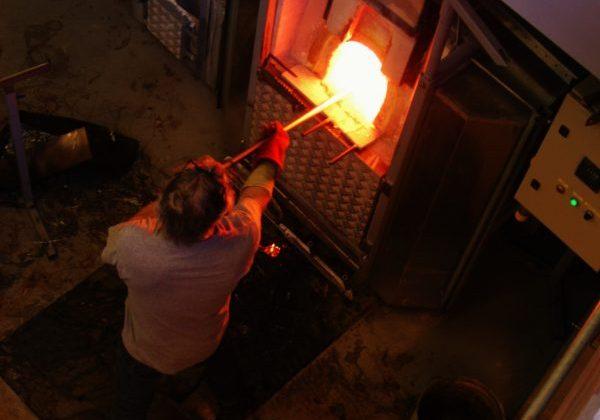 Glaskunstenaar aan het werk met glasoven